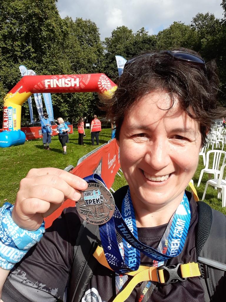 Ellie holding up a medal in the sunshine at the finish line of the Thames Bridges Trek