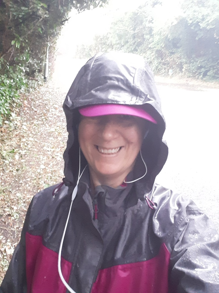 Ellie outside on a tree-lined path in the rain, smiling to the camera